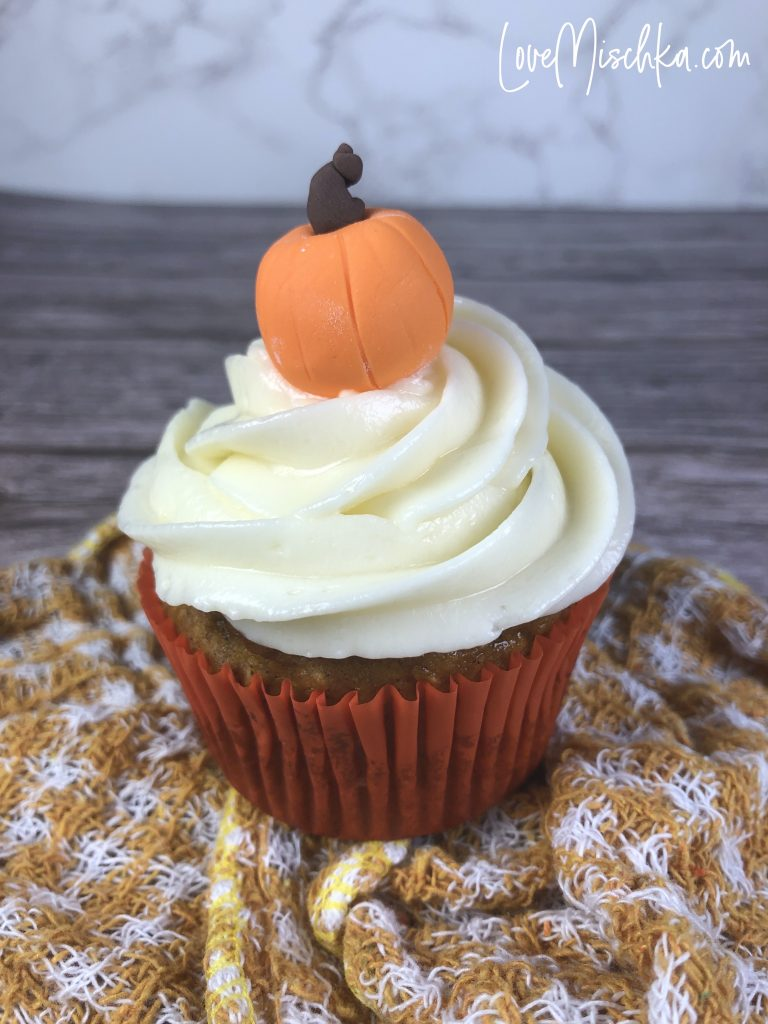 A Cupcake with white swirled frosting and a fondant orange pumpkin on top.