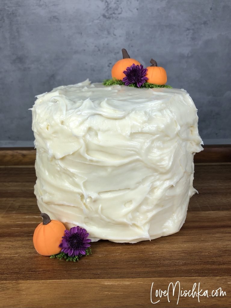 A tall Cake with fluffy frosting with three small pumpkins and two purple flowers.