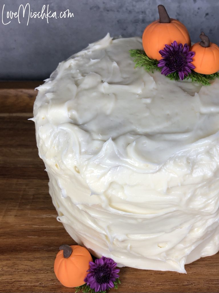 Round Cake with White Creamy Frosting and two small pumpkins.