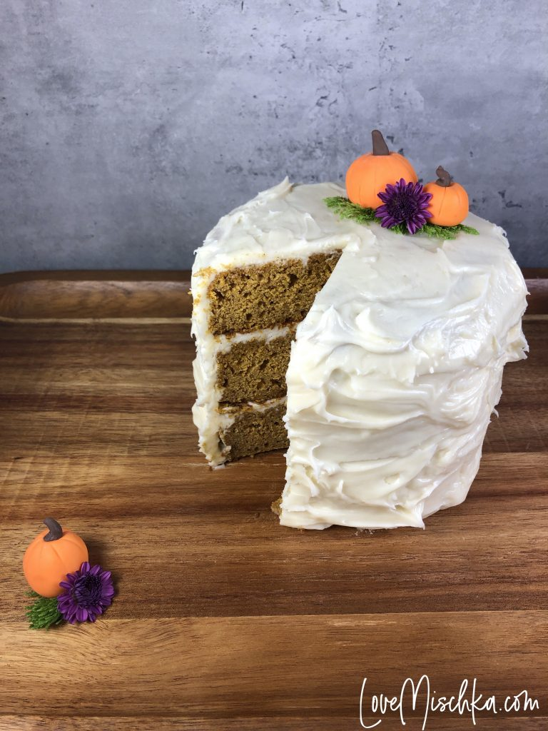 Tall Pumpkin Cake with a Slice Missing. Two Pumpkins on the cake and one on the wooden serving tray.