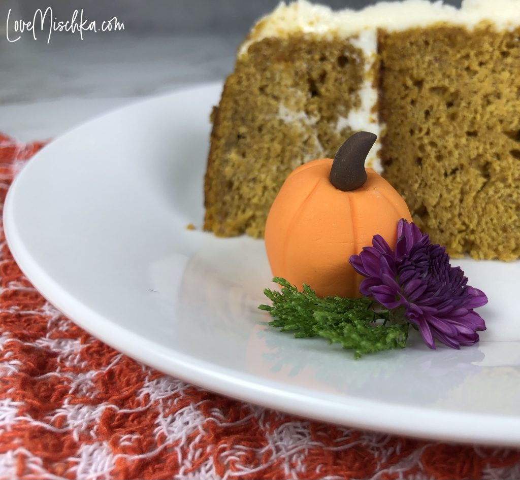 Slice of Pumpkin Cake with Cream Cheese Frosting on a White Plate with a Fondant Orange Pumpkin and real Purple Flower